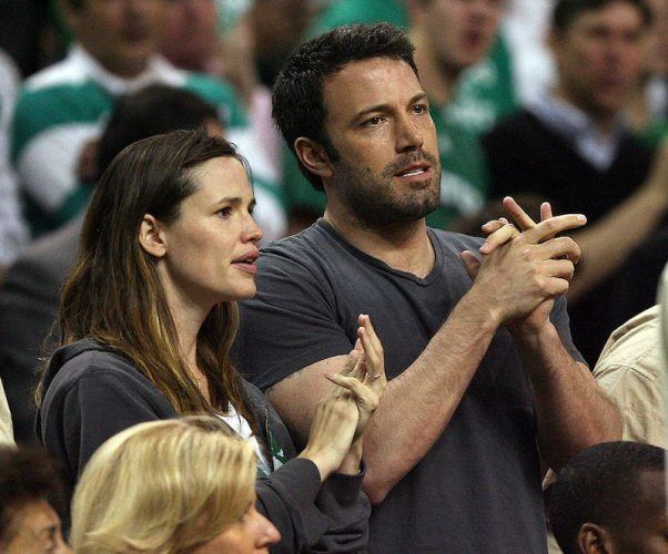 Jennifer Garner and Ben Affleck stand up and clap at a basketball game.