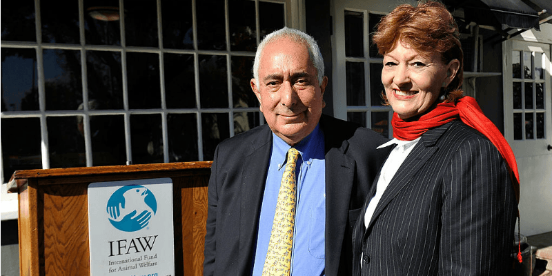 Ben Stein and Alexandra Denman are smiling together in front of a podium.