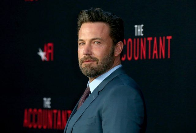 Ben Affleck stands in a blue suit while posing for the paparazzi.