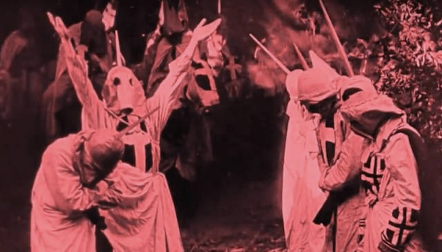 Men in white robes and masks throw up their hands in The Birth of a Nation