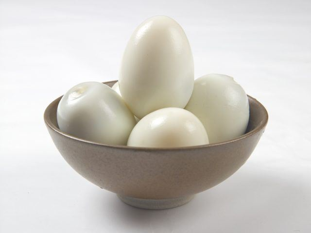 A bunch of eggs in a brown bowl on a white table.