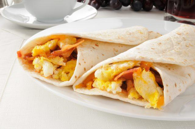 Two breakfast burritos on a white plate.