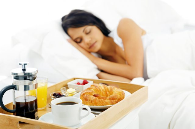 Sleeping woman with breakfast tray served in bed.