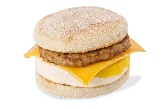 A traditional frozen breakfast sandwich with cheese and sausage patty.