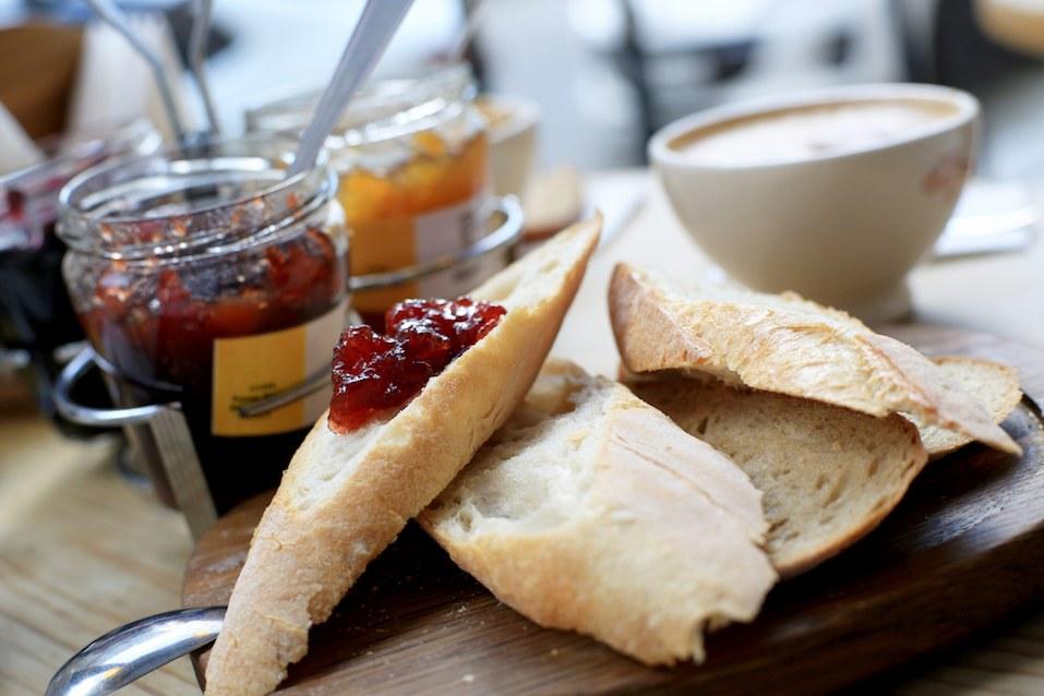 Breakfast, three jars of jam and sliced bread