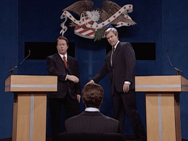 Two men in suits stand next to podiums on stage and shake hands
