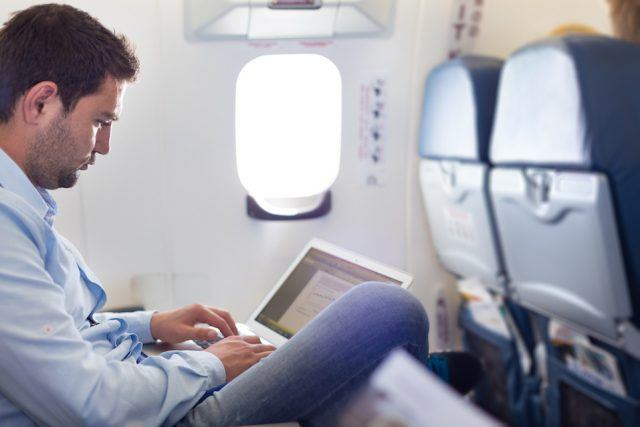Casually dressed middle-aged man working on laptop in aircraft cabin.