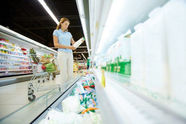 Young female choosing dairy products in supermarket