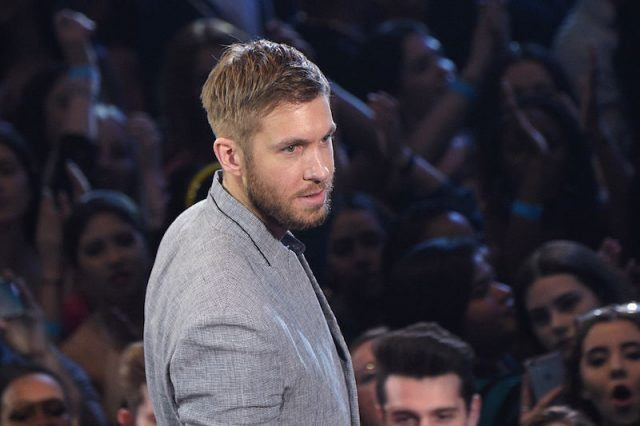 Calvin Harris stands in a grey suit in front of fans.