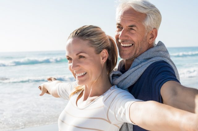Happy senior couple standing on beach with arms outstretched.