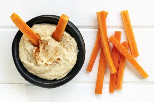 A dish full of hummus and carrot sticks.