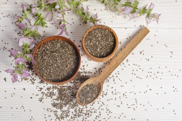 Chia seeds with flowers on a white table.
