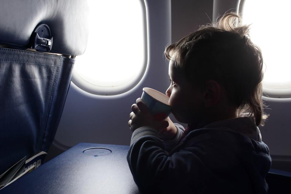 The child drinks tea in the airplane
