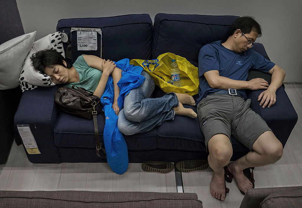 Chinese shoppers sleep on a sofa in the showroom of the IKEA store