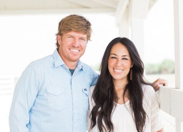 Chip and Joanna Gaines smiling as they stand next to each other.