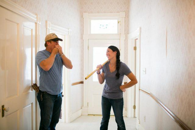 Chip and Joanna Gaines stand in a hallway while laughing.