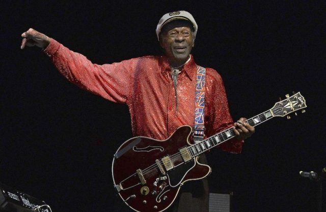 Chuck Berry holds a guitar and sings at a concert in 2013.