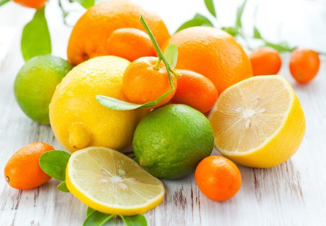 Whole and sliced citrus fruits on a wooden table