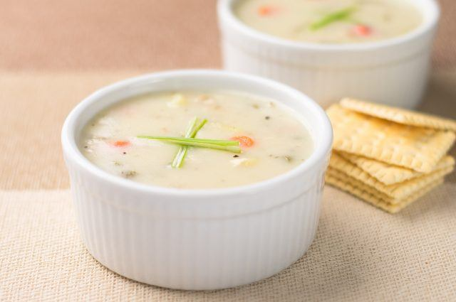 Clam chowder in a white soup dish with crackers in the back.