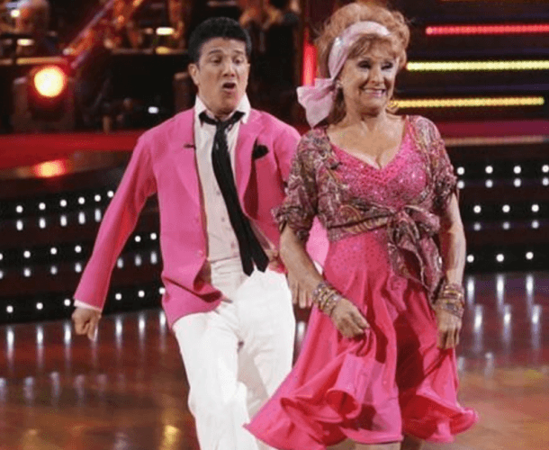 Cloris Leachman and Corky Ballas dancing while wearing pink outfits.