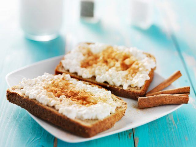 Two slices of whole grain bread with cottage cheese and cinnamon.