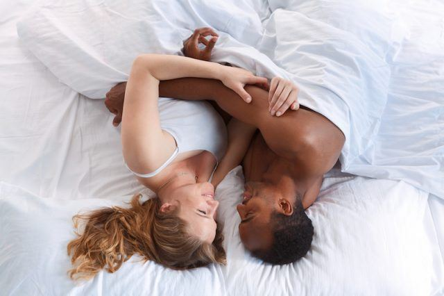 A man and women laying in a white bed together.