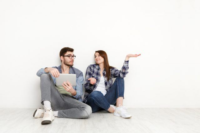 Two people sit together while talking and looking at a tablet.