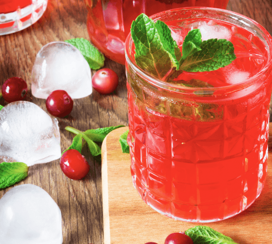 A glass of water with cranberry juice, mint and lemon.