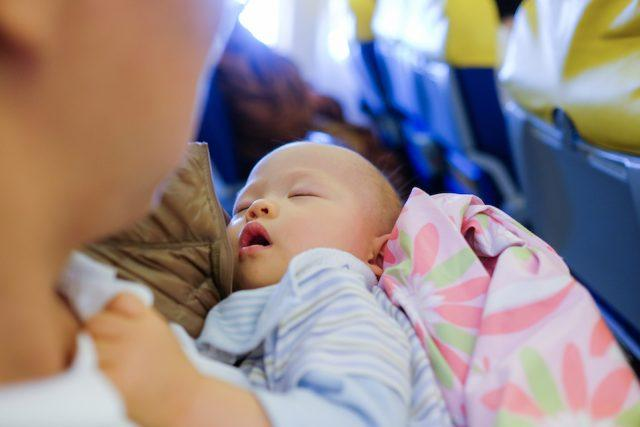 Toddler boy sleeping on father's lap while traveling in airplane.