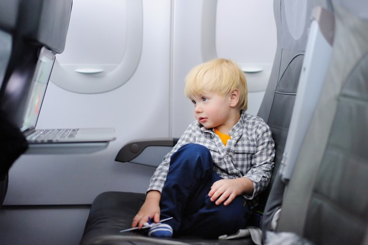 Cute little boy traveling by an airplane