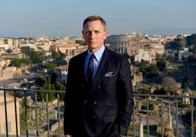 Daniel Craig wears a suit and stands in front of a railing on a balcony