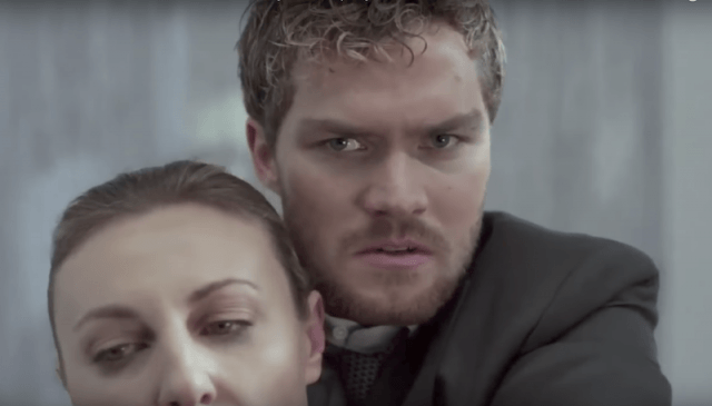Danny Rand holds an enemy in a chokehold.