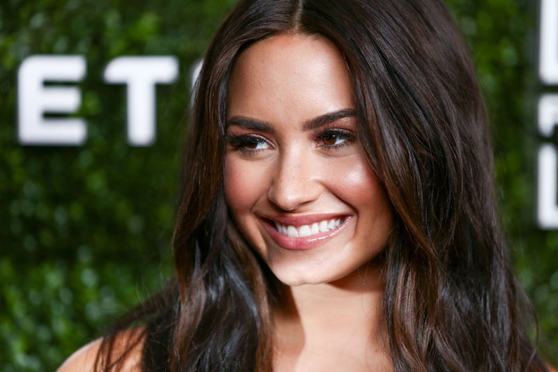 Demi Lovato smiles and looks to the side