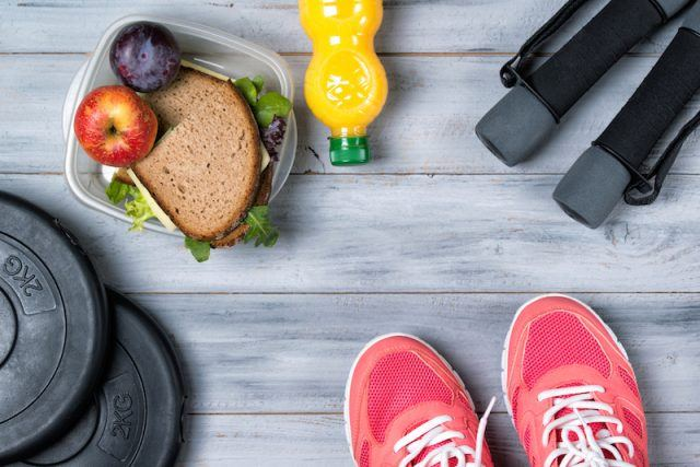 Sneakers, gym equipment, and a healthy lunch seen on a wooden floor.