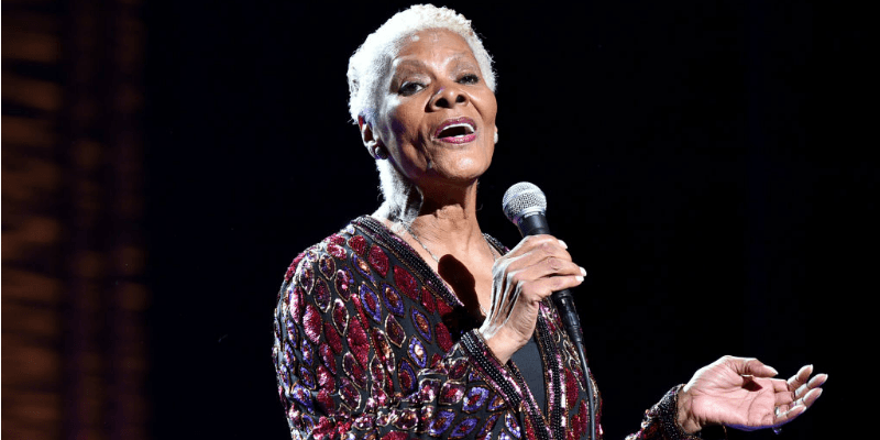 Dionne Warwick sings into a microphone on stage.