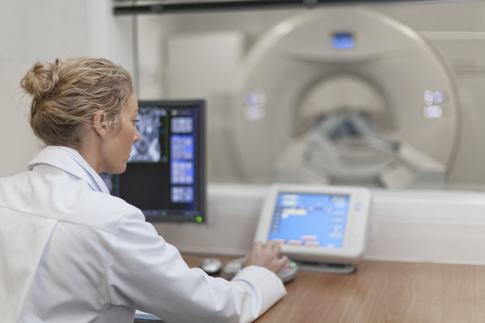 Doctor operating CT scanner