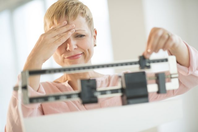 A woman adjusts weighing herself while holding her forehead.
