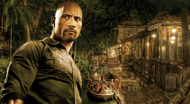 Dwayne Johnson stands with trees, a boat and house in the background