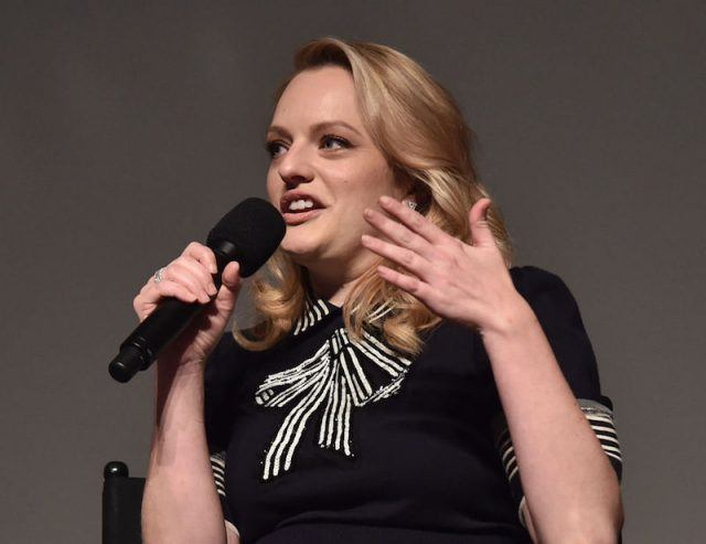 Elizabeth Moss holds a microphone at a press event for 'The Handmade's Tale'.