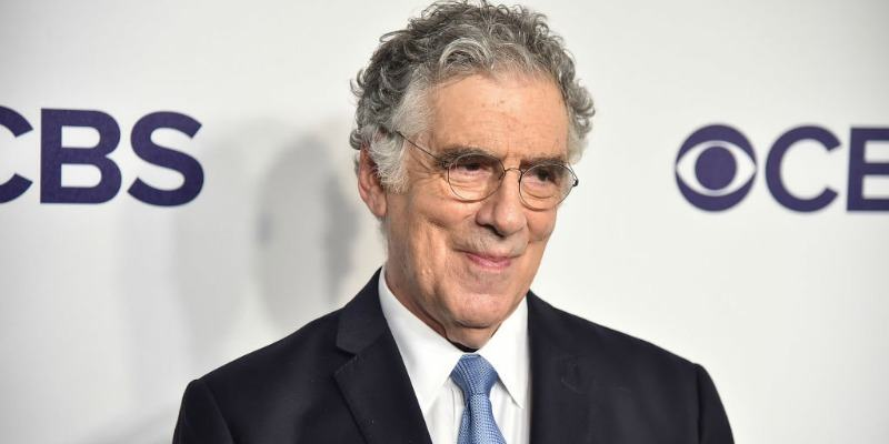 Elliott Gould is smiling in a suit on the red carpet.