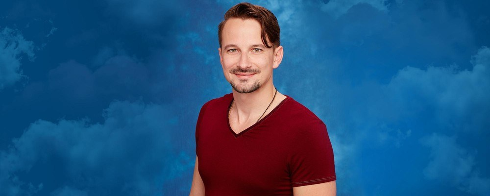 Evan Bass stands in front of a blue background wearing a red shirt.