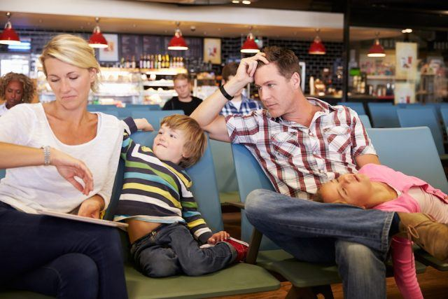 Family In Airport Departure Lounge Wait For Delayed Flight