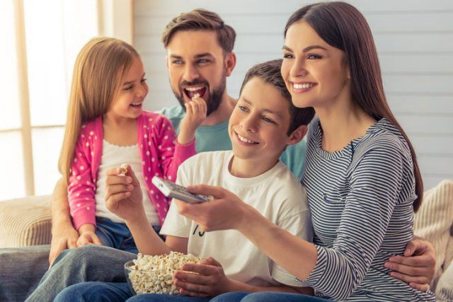 A family sits on a couch together around a bowl of popcorn