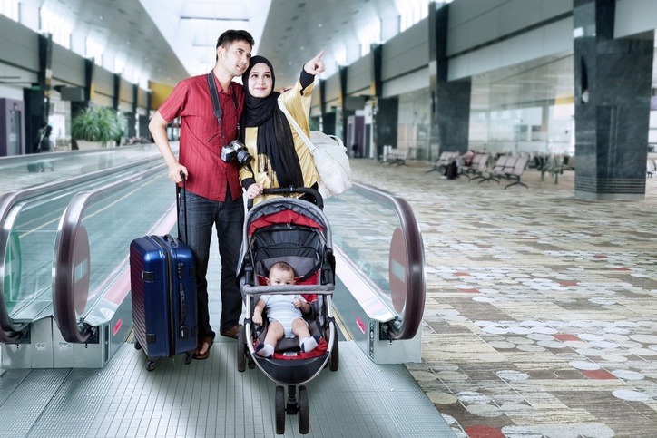 Family with baby standing in the airport hall