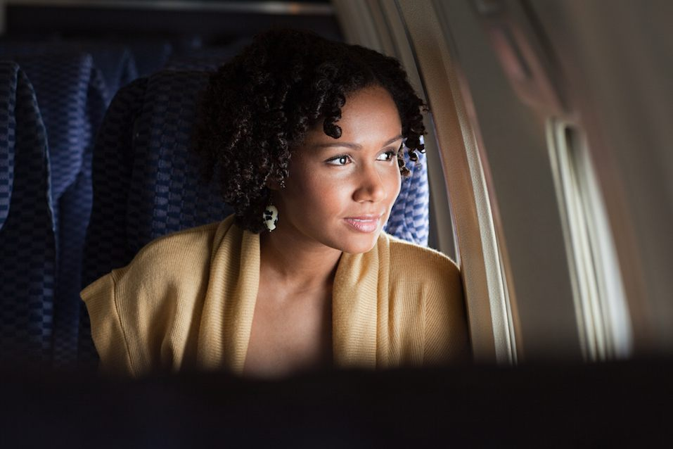 Female airplane passenger looking out of window