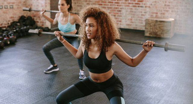 Females workout in gym with barbell.