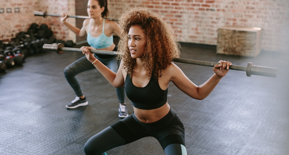 Woman working out in a gym with a barbell
