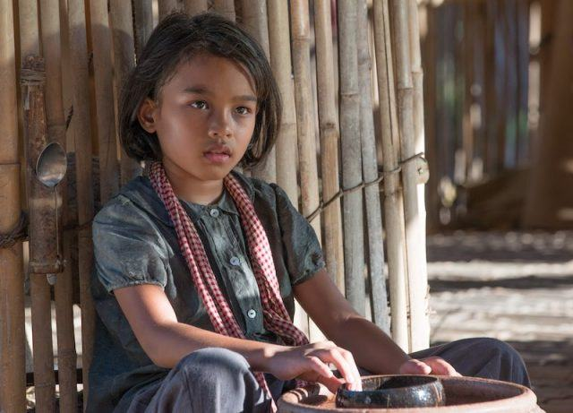 Roland Neveu from 'First They Killed My Father' sits in her village hut.