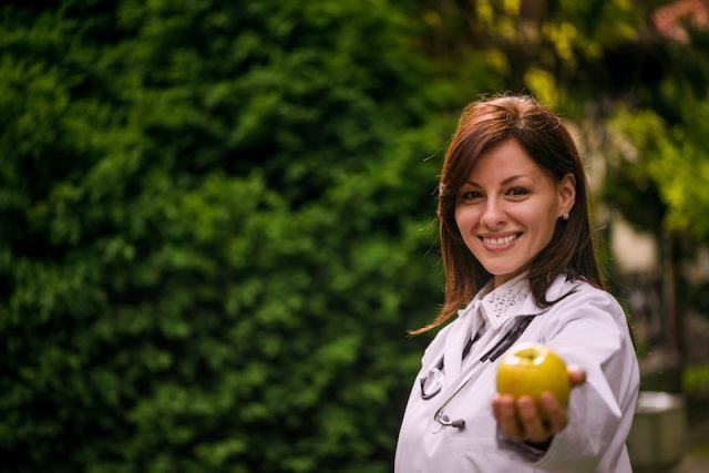 Portrait of a beautiful smiling female doctor offering you an apple