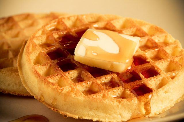 Two frozen waffles on a plate with syrup and butter.